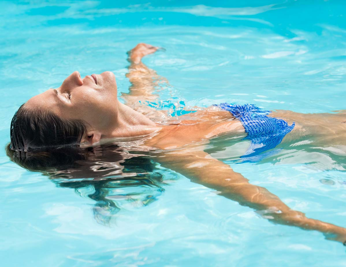 Woman meditating and relaxing in a pool as part of the detox and recovery process